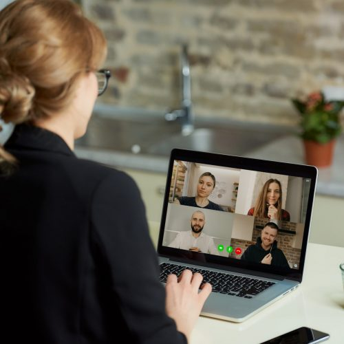 A laptop screen view over a woman's shoulder. A girl works remotely on a computer in her studio. A female professor listening to the answers of the students in an online lesson at home.