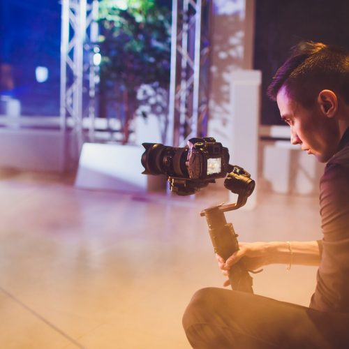 Professional videographer holding camera on 3-axis gimbal. Videographer using steadicam. Pro equipment helps to make high quality video without shaking